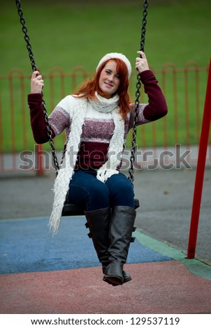 Pretty young red haired female on swing