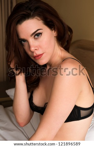 Pretty young redhead dressed in black lingerie - stock photo