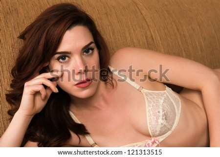 Pretty young redhead dressed in white lingerie - stock photo