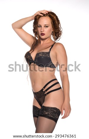 Pretty young redhead in black lingerie on white - stock photo