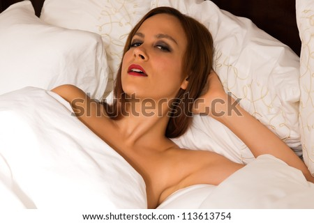 Pretty young redhead lying nude in bed