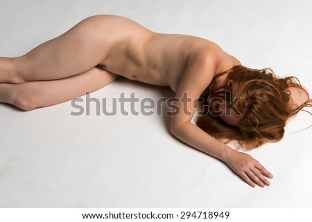 Pretty young redhead nude on gray - stock photo