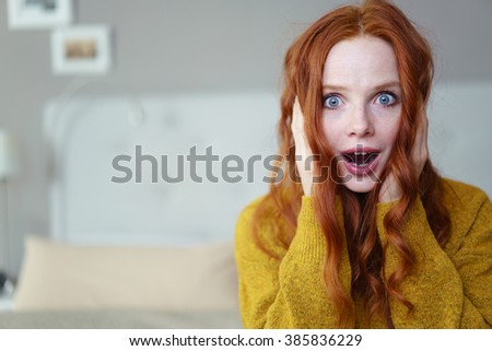 Pretty young redhead woman holding her hands to her cheeks with a look of wide-eyed astonishment or amazement as she sits on her bed at home, with copy space - stock photo