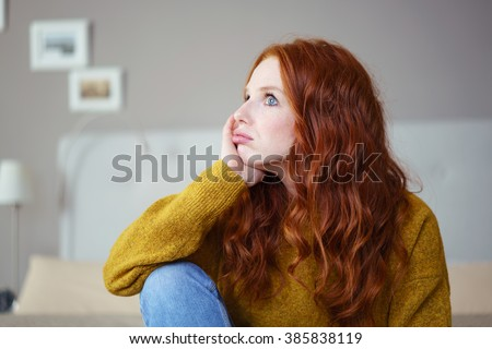 Pretty young redhead woman sitting on her bed with her chin on her hand pouting her lips with a glum expression a s she stares into the distance - stock photo
