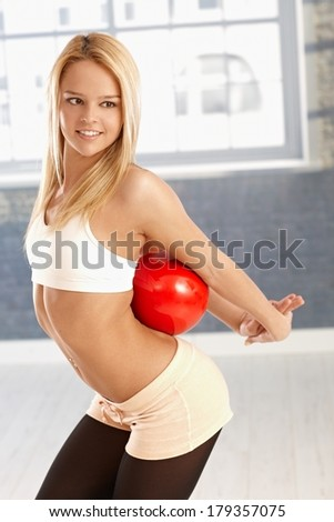 Pretty young rhytmic gymnast exercising with ball, smiling.