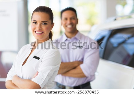 pretty young saleswoman with co-worker on background - stock photo