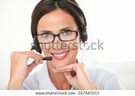 Pretty young secretary with glasses talking on her headset while smiling - close up portrait - stock photo