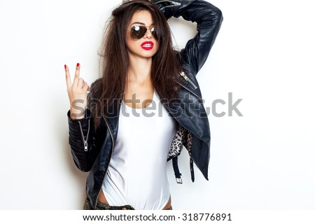 Pretty young sexy fashion sensual woman posing on white wall background dressed in hipster style jeans outfit,Stylish fashionable blonde girl hipster in black clothes.White background,not isolated - stock photo