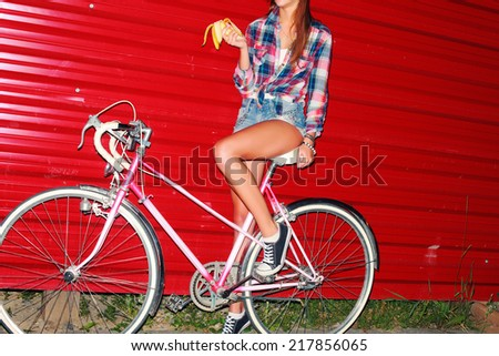Pretty young sexy girl riding bicycle vintage retro style alone on red wall background with eating banana hipster look lifestyle picture  - stock photo