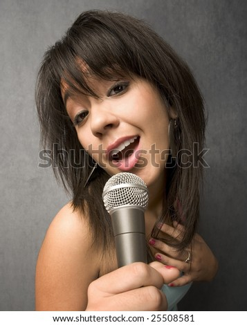 Pretty young singer with a large microphone
