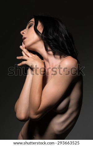 Pretty young slender brunette standing nude on gray - stock photo