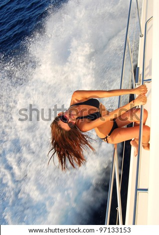 Pretty young slim sexy brunette woman in sunglasses sailboat yacht in black stylish bikini on private speed-boat on vacation in summer time happy sailing in Mediterranean sea - stock photo