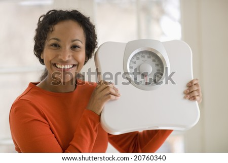 Pretty young smiling Beautiful African American woman holding scale - stock photo