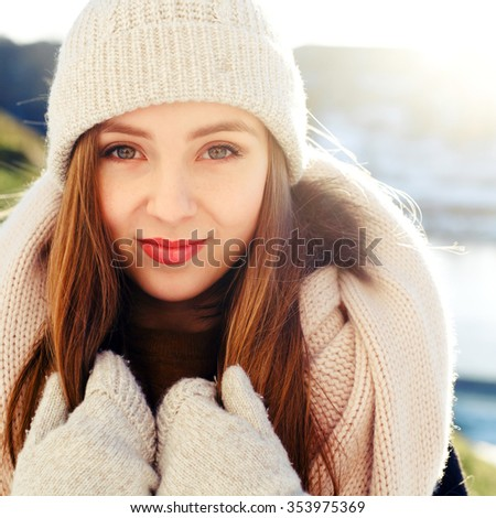 Pretty young smiling brunette woman posing outdoor on the street fashion closeup portrait winter clod style
