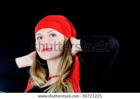 Pretty young smiling fortuneteller, on black backgund - stock photo