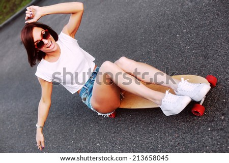 Pretty young smiling happy laughing girl dressed in jeans shorts and white T-shirt sitting on long-board and having fun. Downhill, longboarding . Outdoors, lifestyle.  - stock photo