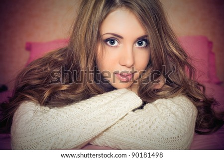 Pretty young smiling woman in winter sweater - stock photo
