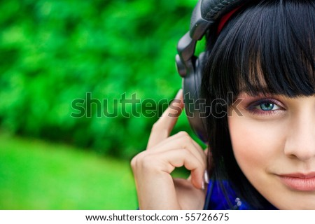 pretty young smiling woman listening music - stock photo