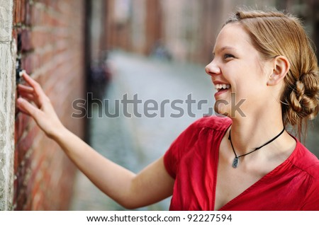 Pretty young smiling woman ringing at the door bell