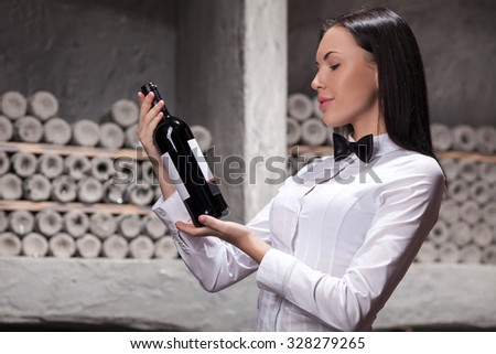 Pretty young sommelier is standing in cellar and holding a bottle of red wine. The woman is looking at it and examining wine. She is smiling - stock photo