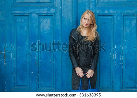 Pretty young stylish blonde woman standing against vintage blue  - stock photo