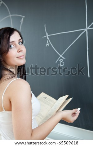 pretty young teacher/college student drawing on the chalkboard/blackboard during a math class (shallow DOF; color toned image) - stock photo