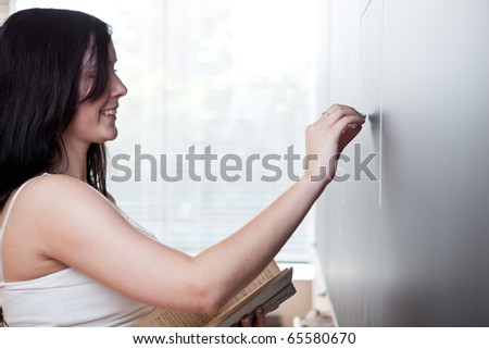 pretty young teacher/college student drawing on the chalkboard/blackboard during a math class (shallow DOF; color toned image)