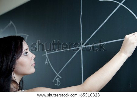 pretty young teacher drawing on the chalkboard/blackboard during a math class (shallow DOF; color toned image) - stock photo