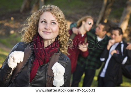 Pretty Young Teen Girl with Three Boys Behind Admiring Her. - stock photo