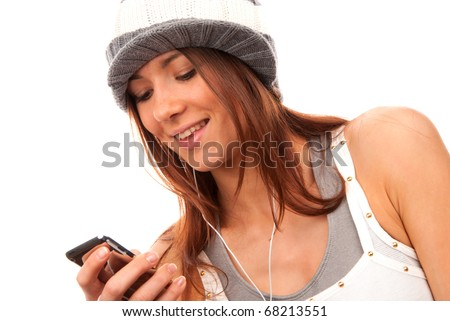 Pretty young teenage girl typing and reading text message on her new modern cell phone mobile and listening music in headphones isolated on a white background - stock photo
