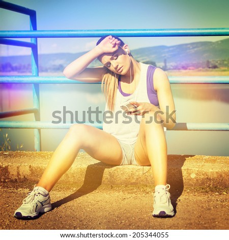 Pretty young tired Caucasian blonde jogger woman with smart phone sitting relaxing outdoors wiping her face relaxing after running. Square format image, instagram filter. Color filter applied. - stock photo