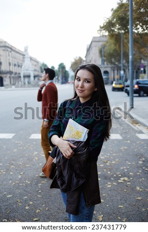 Pretty young tourist girl holding city map in the hands standing on the road, young traveler girl standing with the map looking to the camera, charming hipster girl traveling alone - stock photo