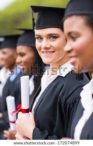 pretty young university graduate standing in a row - stock photo