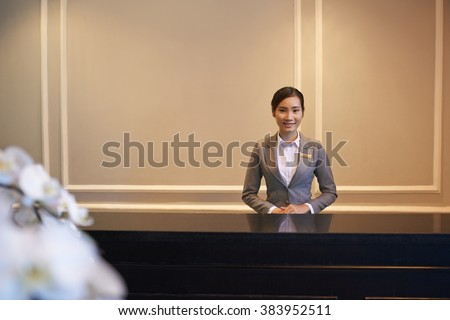 Pretty young Vietnamese girl standing at hotel reception