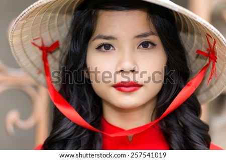 Pretty young Vietnamese woman in a red top with matching lipstick wearing straw hat, close up face portrait looking into the camera - stock photo