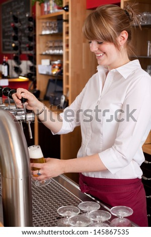 Pretty young waitress serving draft beer standing behind the bar counter dispensing it into a pint glass from a metal spigot - stock photo
