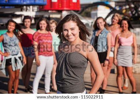 Pretty young white teenage girl standing near friends at theme park - stock photo