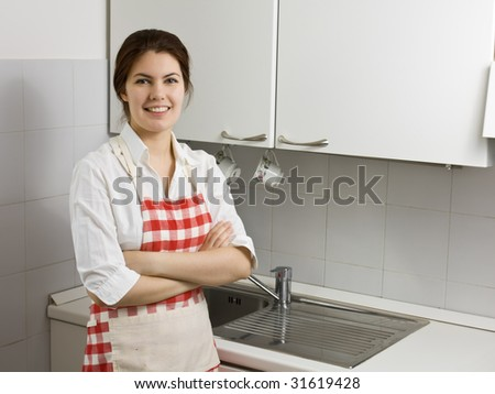 Pretty young woman alone in the kitchen - stock photo