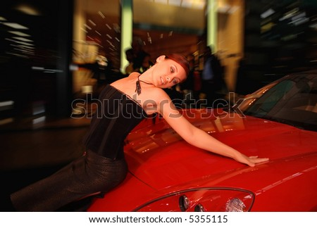 Pretty young woman and a red sports car. - stock photo