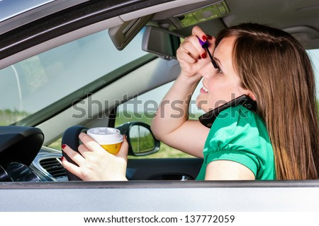 Pretty young woman applying makeup, speaking on phone and drinking coffee while driving her car - stock photo