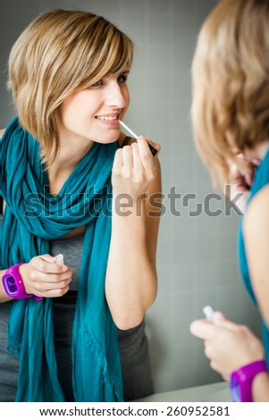 Pretty, young woman applying mascara /eyeshadows in front of a mirror - stock photo