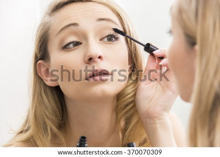 Pretty young woman applying mascara to her eyelashes with a brush applicator from a tube she is holding, focus to her hand and reflection in the mirror