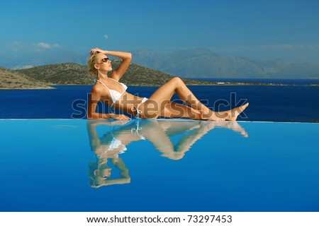 Pretty young woman at a swimming pool - stock photo