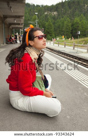 Pretty young woman at a Swiss station waiting for a train. - stock photo