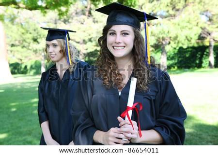 Pretty young woman at graduation holding diploma - stock photo
