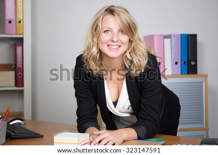 Pretty young woman at office looking at the camera
