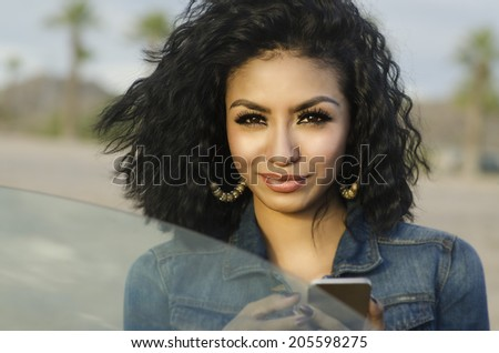 Pretty young woman beside her car making phone call - stock photo
