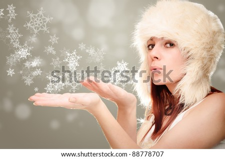 pretty young woman blowing on the stars on her hands - stock photo