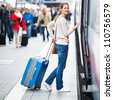 Pretty young woman boarding a train - stock photo