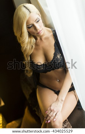 Pretty young woman by the window in black lingerie
